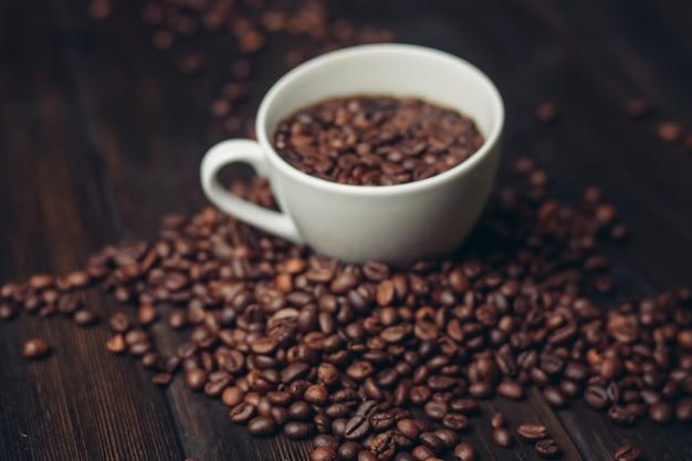 コーヒー豆の香りのよい飲み物の朝のエネルギーと白いカップ。
