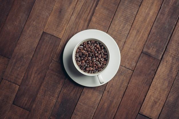 コーヒー豆の香りのよい飲み物の朝のエネルギーと白いカップ