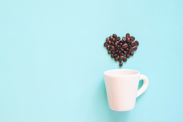 White cup with coffee beans arranged in heart shape on pastel colour background