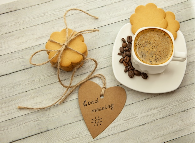 White cup with coffee, coffee beans and ginger biscuits, tasty breakfast concept