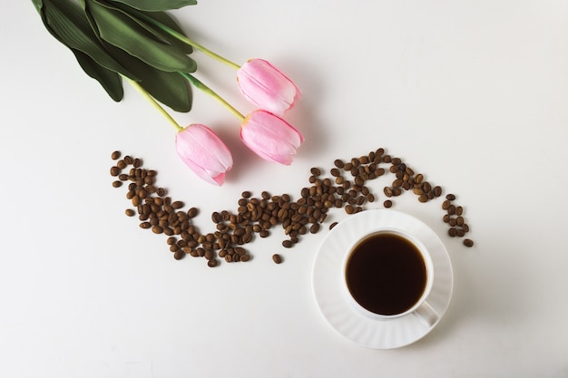 White cup with coffee, coffee beans, tulips on a white surface. flat lay, top view