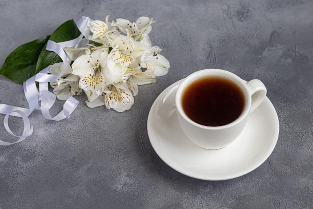 회색 배경에 커피와 함께 흰색 컵입니다. 배경에 리본으로 묶인 난초의 꽃다발. 배너, 휴일 축하합니다. 공간을 복사하십시오.