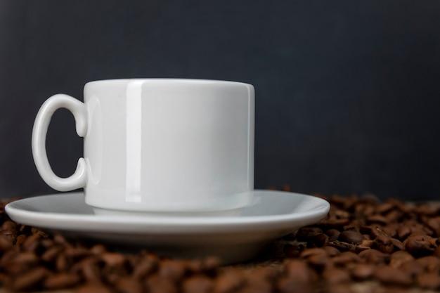 ふりかけた焙煎豆にコーヒーと白いカップ。
