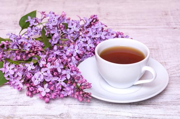 コーヒーまたは紅茶とライラックの花束と白いカップ