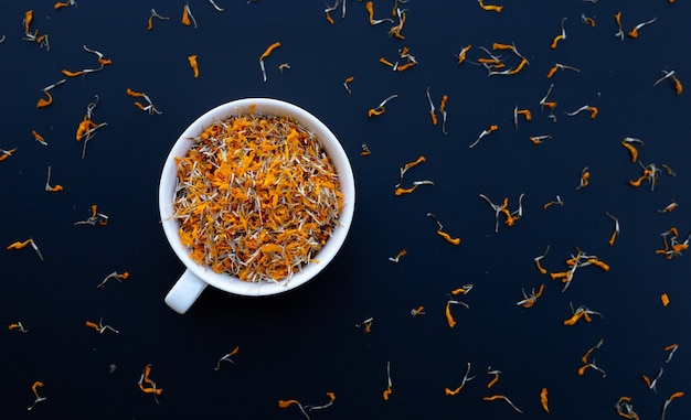 White cup with dry marigold flower petals