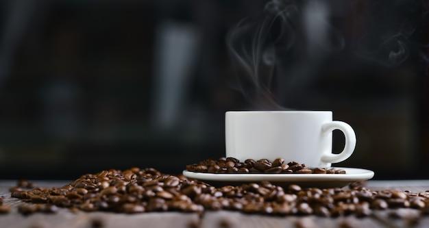Белая чашка с кофе эспрессо и зерна на деревянном темном столе