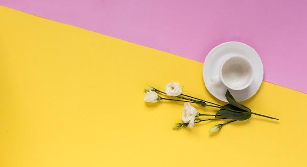 黄色とピンクの背景に花模様の白いカップとコピースペース。