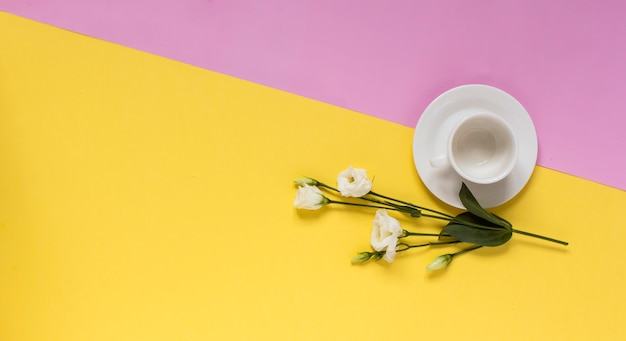 White cup with flowers on a yellow and pink background with copy space.