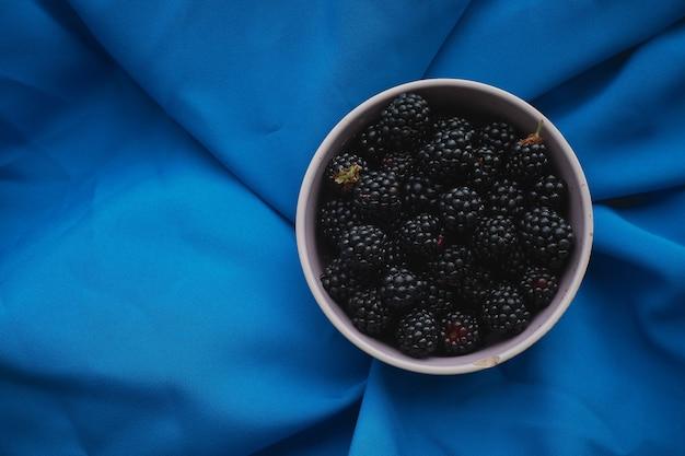 青い布に新鮮なブラックベリーと白いカップ