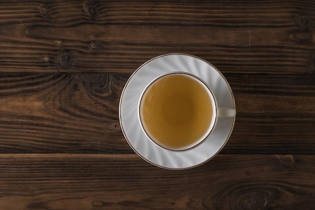 Белая чашка с зеленым чаем на деревянном столе. бодрящий напиток, полезный для здоровья.