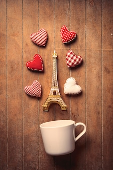 White cup with heart shapes and eiffel tower toy