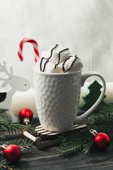 창턱에 크리스마스 훈장을 가진 핫 초콜릿과 마쉬 멜 로우 화이트 컵.