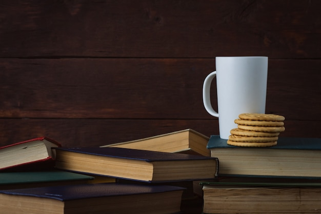 White cup with hot coffee, cookies on deployed books on a dark wooden background