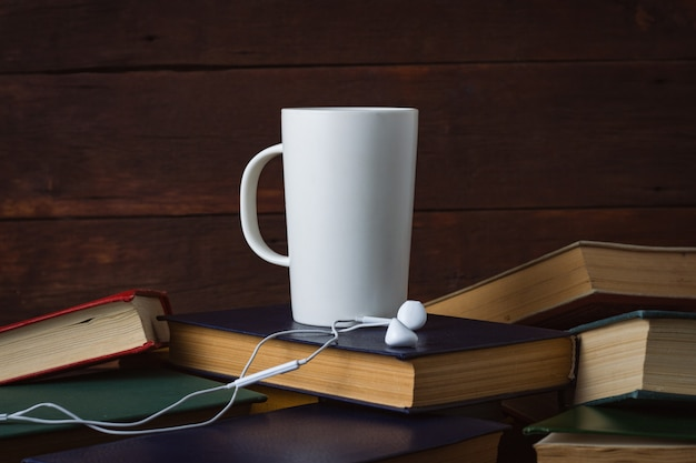 White cup with hot coffee and headphones on deployed books on a dark wooden wall