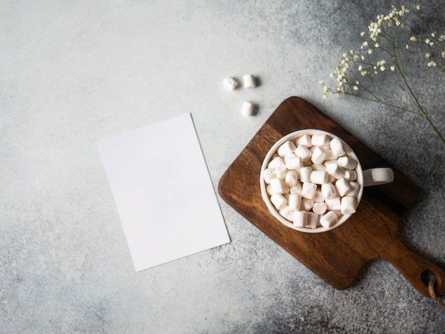 White cup with hot drink and marshmallows and flowers and white card on a grey background. copy space. top view