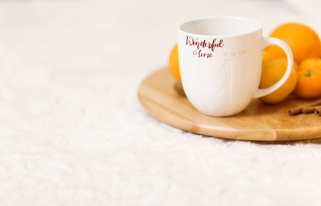 A white cup with the inscription wonderful winter stands on a wooden tray