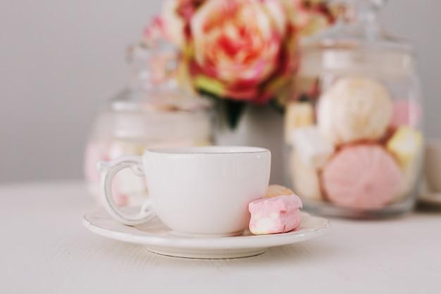 Белая чашка с зефиром на белом фоне. романтический завтрак. концепция праздника, дня рождения, пасхи, 14 февраля, 8 марта. плоская планировка