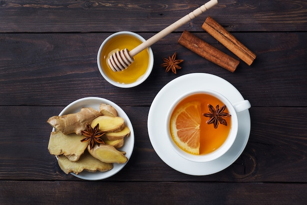 White cup with natural herbal tea ginger lemon and honey cinnamon