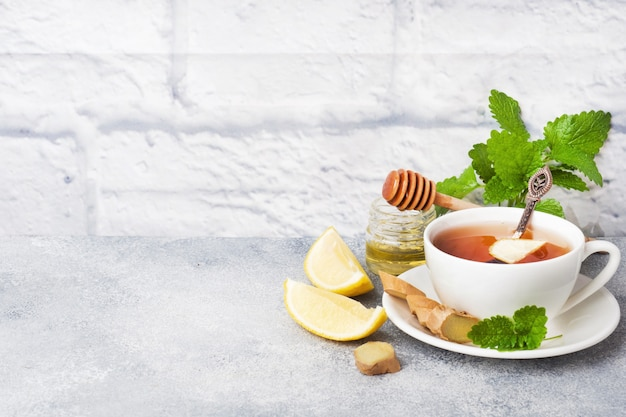 White cup with natural herbal tea ginger lemon mint and honey.