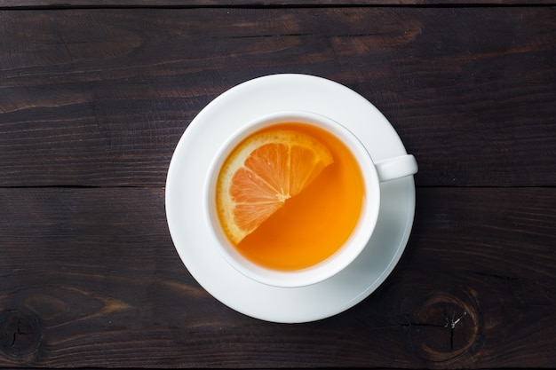 White cup with natural herbal tea with lemon cinnamon