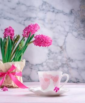 회색 대리석의 배경에 대해 테이블에 봄 꽃의 꽃병과 핑크 하트와 흰색 컵. 모닝커피, 아침식사.