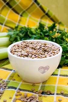 White cup with raw lentils on natural vegetable background