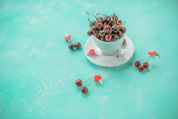 White cup with ripe berries of red sweet cherry and several berries in front of the cup