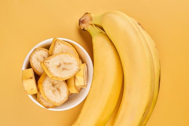 Белая чашка с нарезанными бананами на желтом фоне. тропические фрукты, здоровое питание, витамины