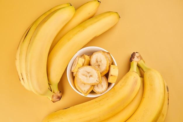 노란색 배경에 얇게 썬 바나나가 있는 흰색 컵. 열대 과일, 건강 식품, 비타민