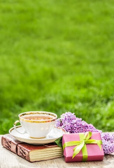 White cup with tea, flowers and gift box