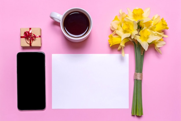 A white cup with tea, a gift with a red ribbon, a piece of paper, mobile phone and a bouquet of daffodils on a pink background. flat lay design, top view.