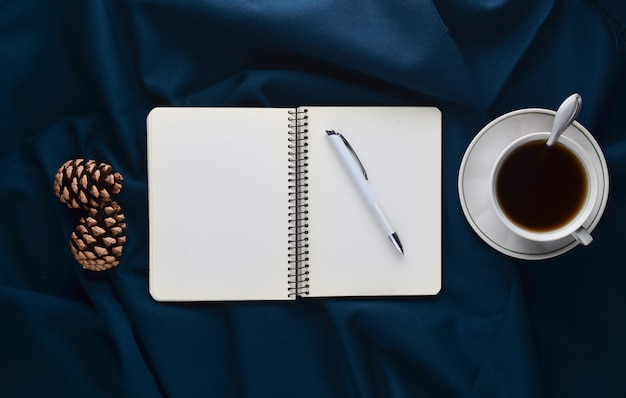 White cup with tea, notebook and pen, pine cones on a dark sheet. winter morning tea drinking. top view. flat lay. minimalism trend.