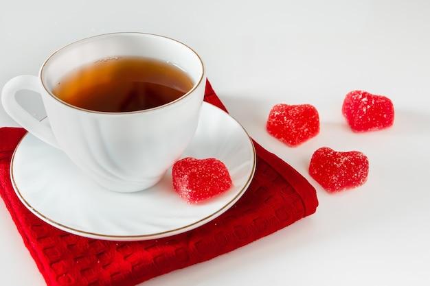 Белая чашка с чаем на красной салфетке и мармелад в форме сердца на белом фоне. символ любви, день святого валентина, подарочная карта