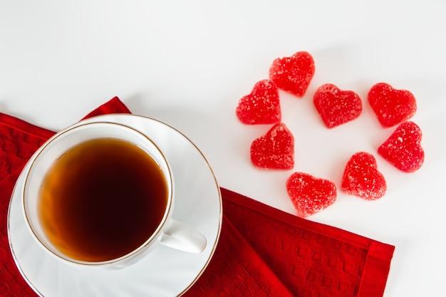Белая чашка с чаем на красной салфетке и мармелад в форме сердца на белом фоне