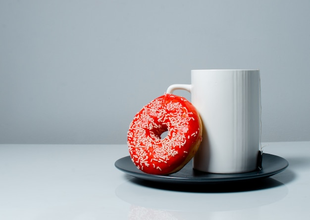 White cup with tea and a sweet colored donut. work from home concept