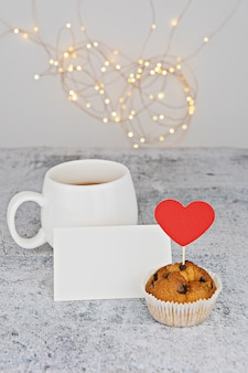 White cup with valentine chocolate candy red hearts and muffin