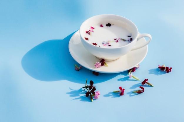 青い背景にビーガンミルクと花と白いカップ。ベジタリアンドリンクとフード、ハーブティー、美容と健康、スパのコンセプト。