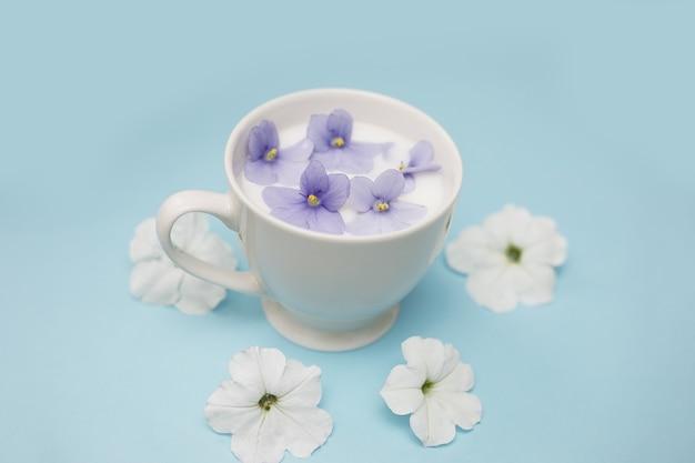 青い背景にビーガンミルクと花と白いカップ。ベジタリアンの飲み物と食べ物、ハーブティー、美しさと健康の概念。スパサロン、コピースペース。クローズアップ写真。システムをフラッシュします