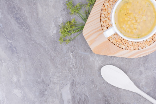 A white cup of yellow pea soup in a wooden platter.