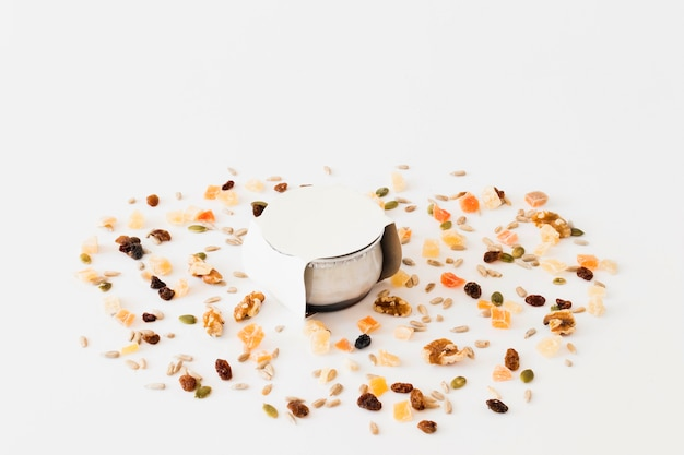 White cup for yogurt between nuts and raisins