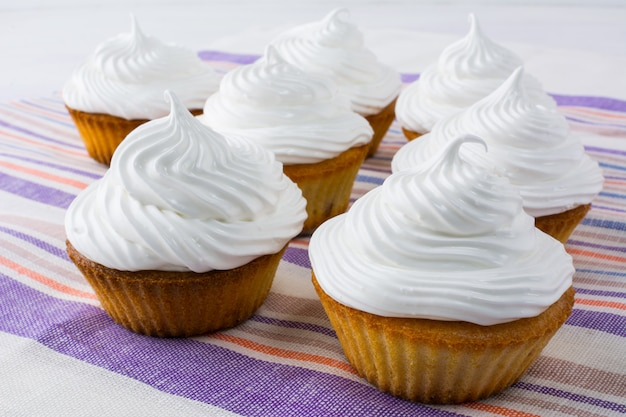 White cupcakes on the striped linen napkin