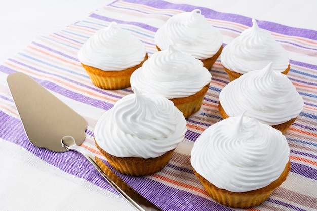 White cupcakes on the striped napkin