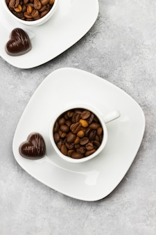 White cups for espresso filled with coffee beans and chocolate in form of heart on a light background. top view.