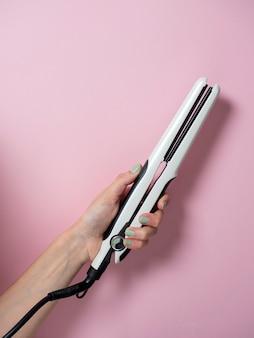 Белая щипцы для завивки в женской руке на фоне pnk. аксессуар для создания прически. красота и мода. уход за волосами.