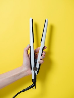 Белая щипцы для завивки в женской руке на желтом фоне. аксессуар для создания прически. красота и мода. уход за волосами.