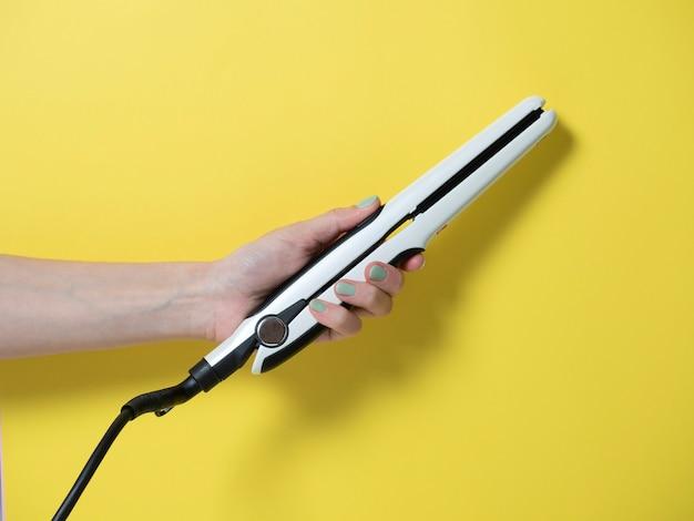 Белая щипцы для завивки в женской руке на желтом фоне. аксессуар для создания прически.