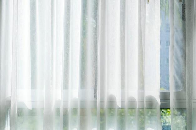 Белая штора у окна с солнечным светом