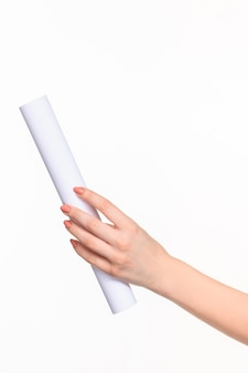 White cylinder of the props in the female hands on white background