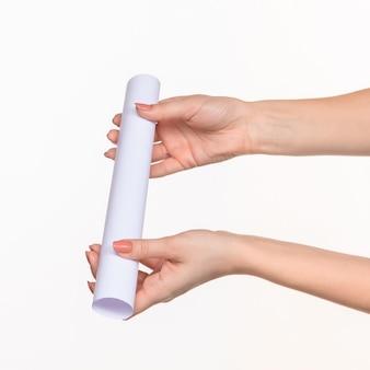 Cilindro bianco di oggetti di scena in mani femminili su bianco con ombra a destra