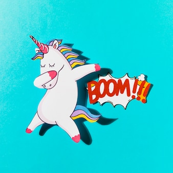 White dabbing unicorn with boom comic text on blue backdrop